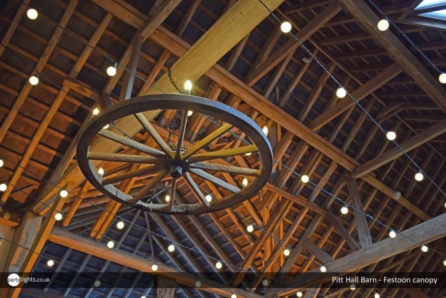 Light bulb canopies decorating a barn interior