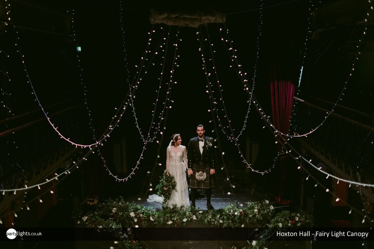 Married couple stood on a stage decorated with draping fairy lights