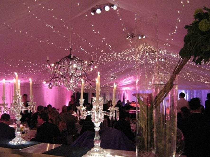 Wedding venue lit up with pink lights and draping fairy lights