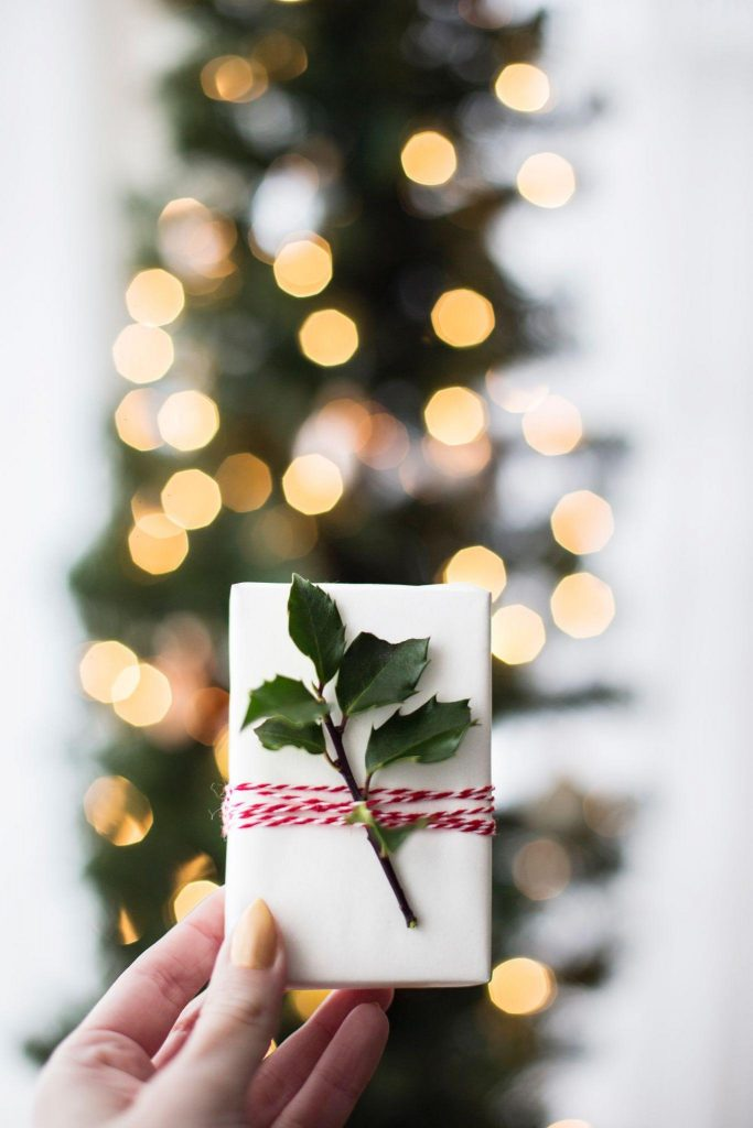 Woman holding a bar os soap with holly leaves tied to it