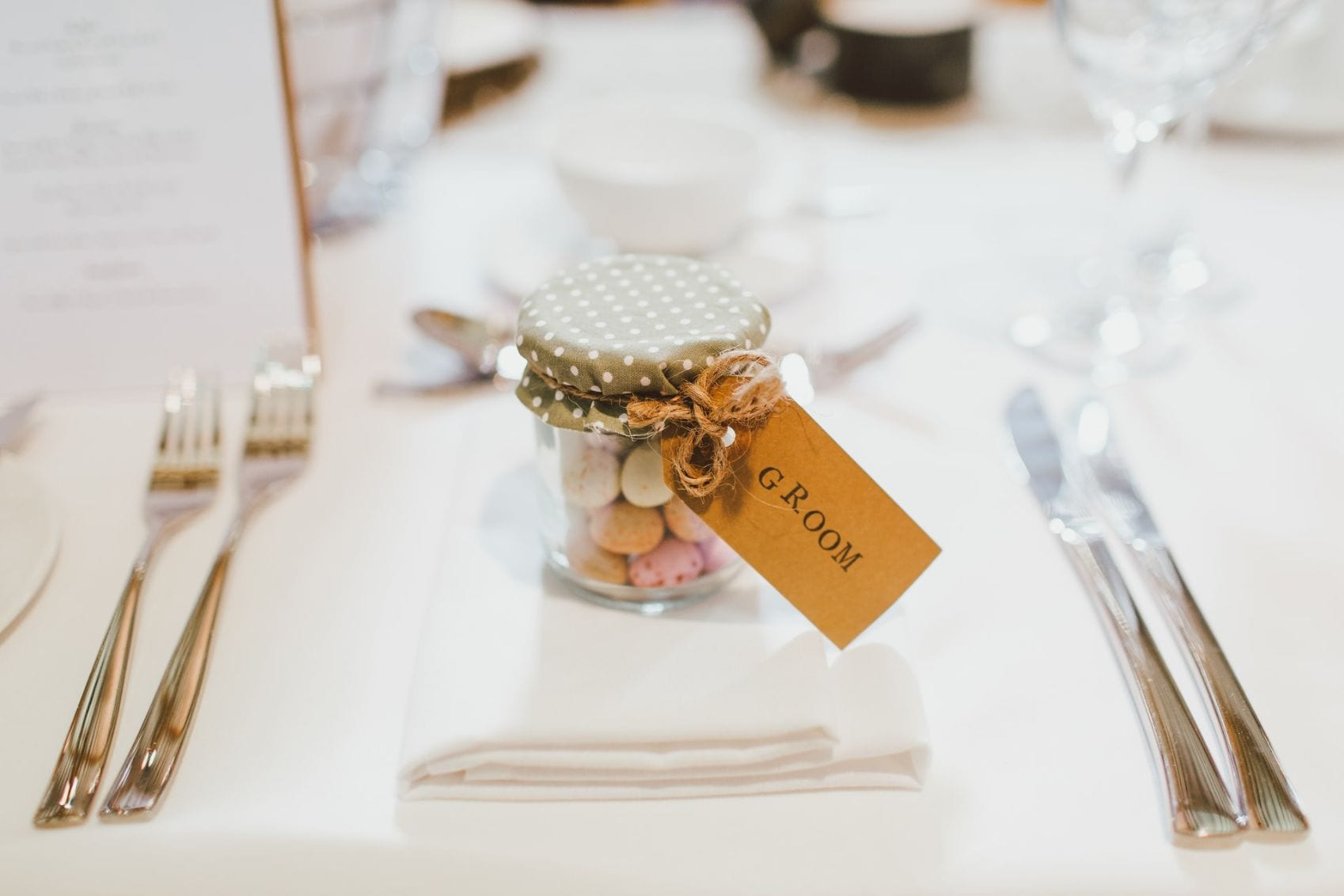 Close up of a Grooms wedding favour- a jar filled with sweets.