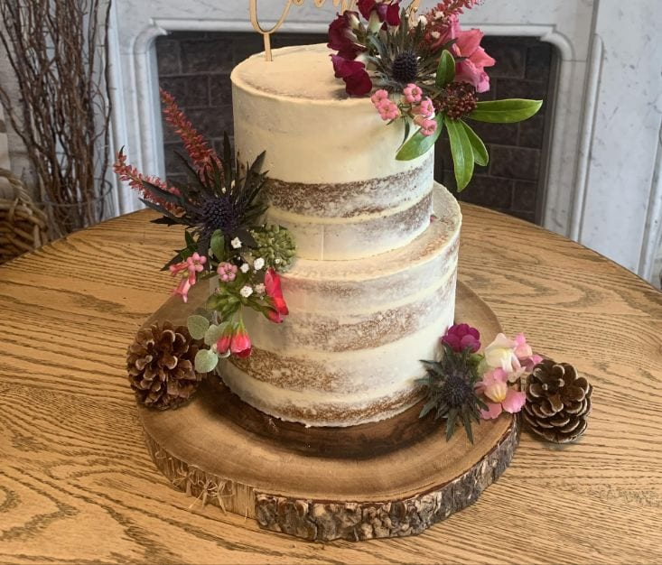 Rustic wedding cake decorated with flowers and pine cones