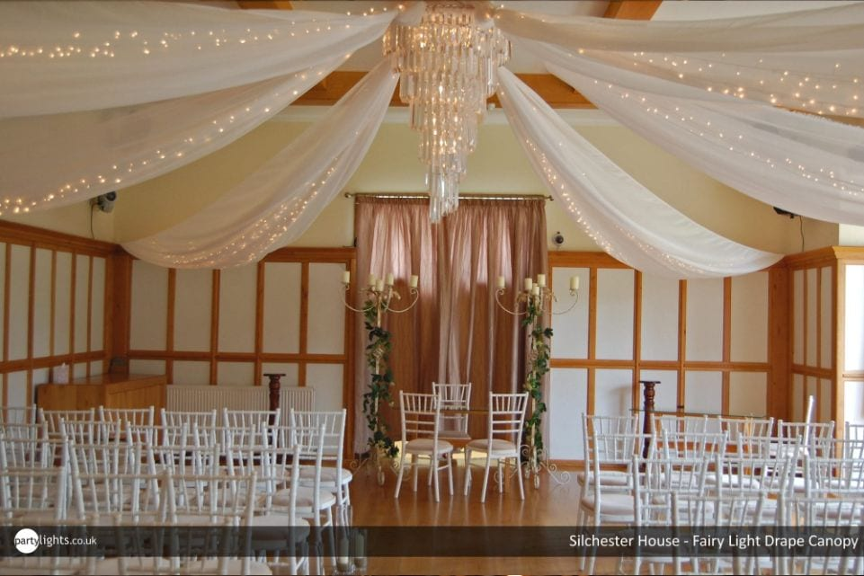 chandelier with fairy lit drapes over a wedding venue with chairs