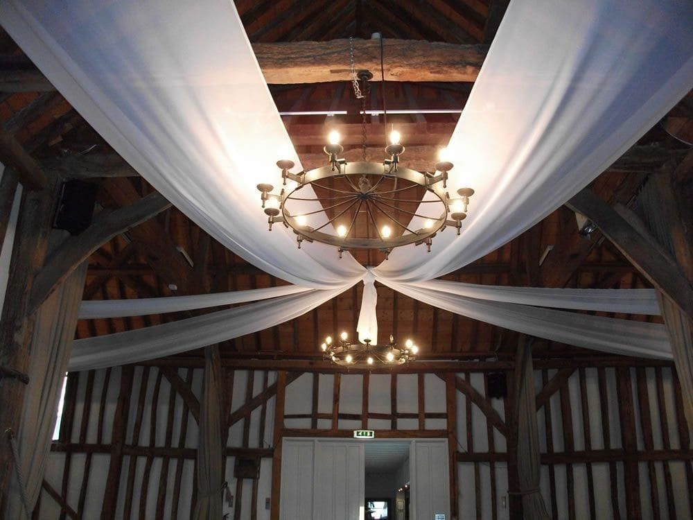 Chandelier with white drapes on the ceiling