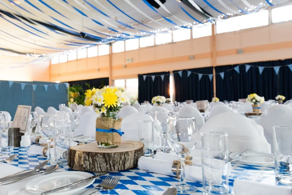 Wedding table decorated with blue table cloth, wooden details, plates, cutlery and wine glasses